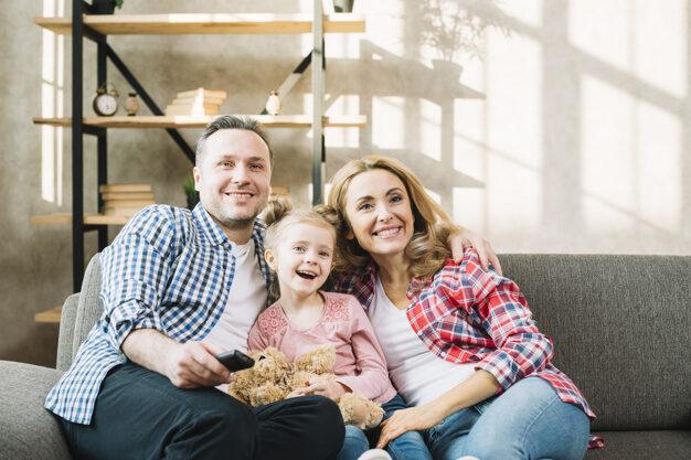 O pai e a mão sentados no sofá com a filha entre os dois. O homem tem um controle remoto na mão e eles assistem televisão.