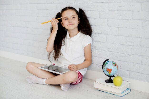 Menina sentada no chão com um tablet no colo com uma expressão sonhadora.