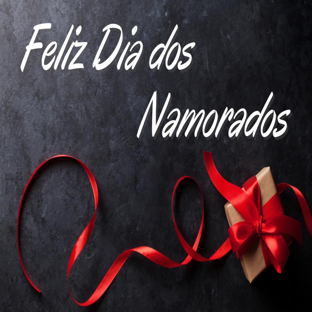 """Caixa marrom enrolada em um longo laço vermelho. Acima dela, lê-se as palavras """"Feliz dia dos namorados""""."""