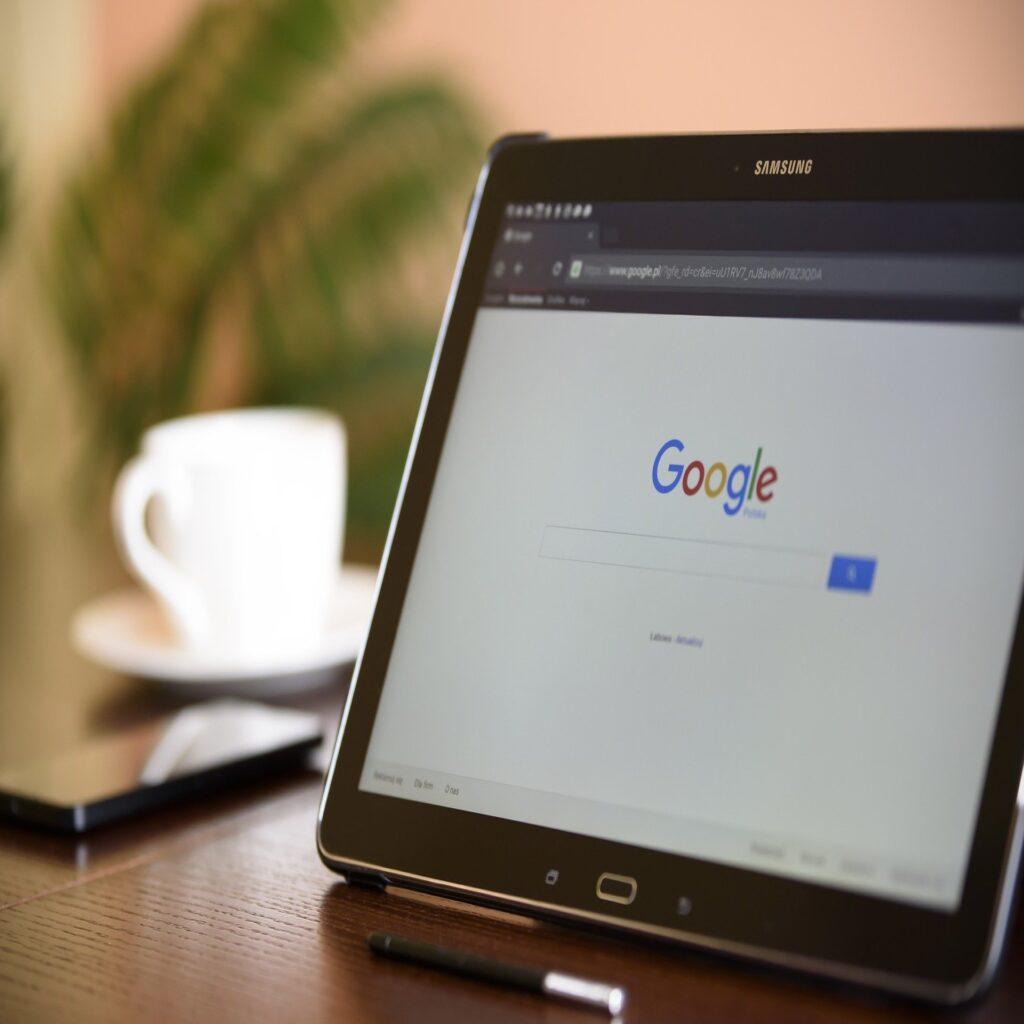 Tablet com a página inicial do Google Chrome aberta em cima de uma mesa de madeira. Ao fundo, pode-se ver um celular e uma xícara desfocados.