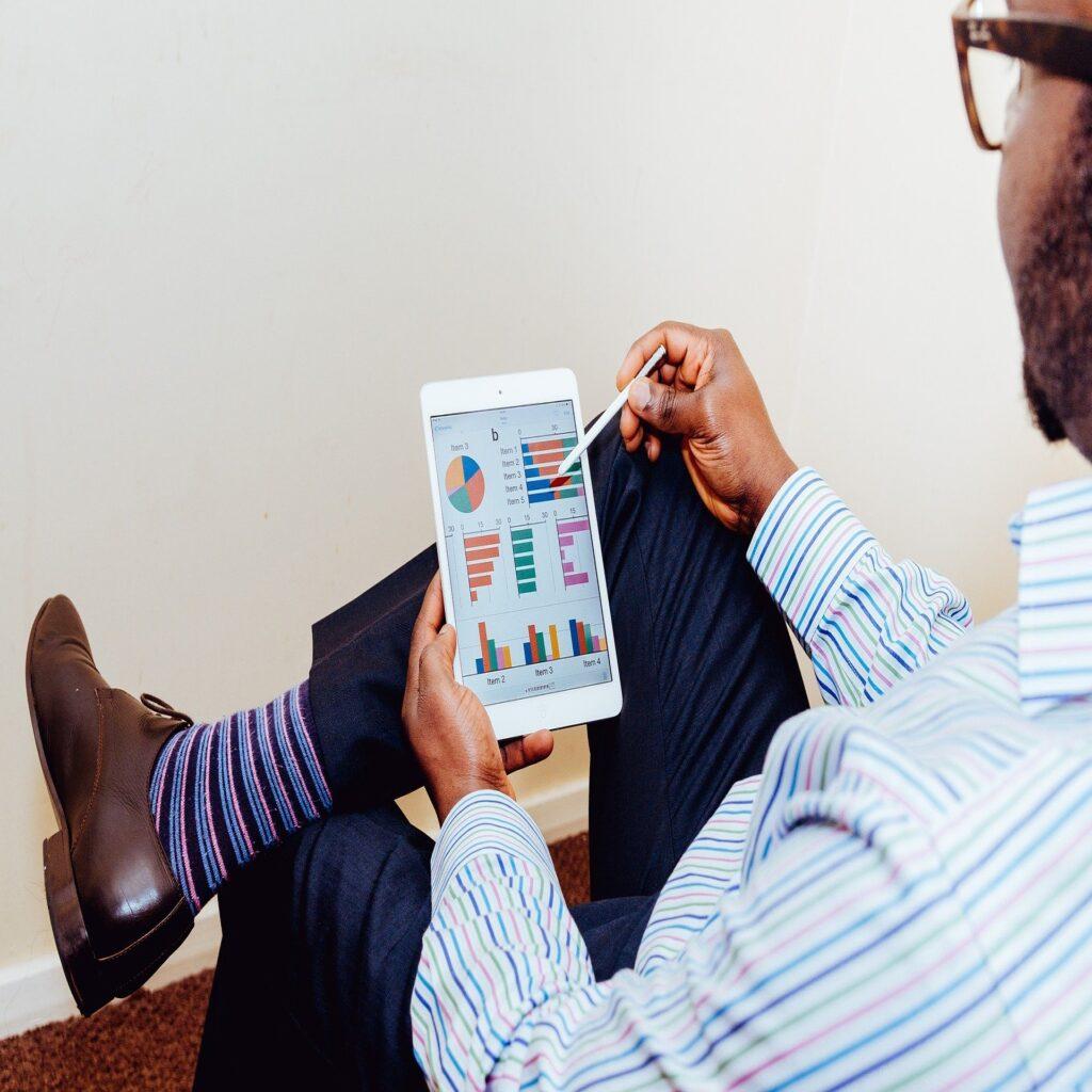 Homem de óculos com as pernas cruzadas analisando gráficos em seu tablet, o qual segura com sua mão esquerda. Na mão direita, o homem tem uma S Pen.