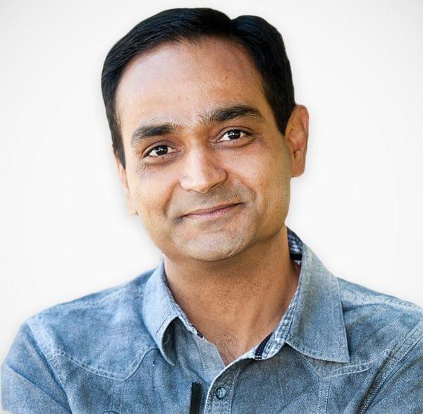 No centro da fotografia está Avinash Kaushik. Um homem indiano de cabelos castanhos escuro e olhos também castanhos. Vestindo uma camisa jeans azul.