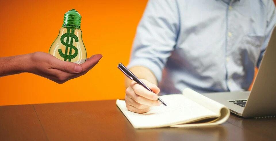 Foto com fundo em cor laranja. Do lado esquerdo temos uma mão segurando uma lâmpada em tons verdes com um cifrão desenhado dentro. Do centro para a esquerda, um homem usando uma camisa azul claro, escrevendo em um caderno e mexendo em um notebook cinza.