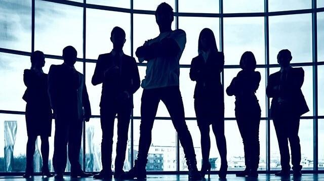 No centro da fotografia está a silhueta de sete pessoas. São quatro homens e três mulheres posicionados lado a lado em linha reta. Eles estão em frente a vidraça de um prédio corporativo.