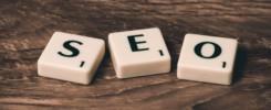 """Peças brancas, com uma letra cada uma, todas escritas em preto, dispostas em cima de uma mesa formando a sigla """"SEO""""."""
