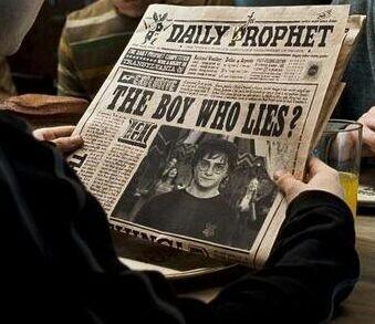 """Harry Potter lendo no Profeta Diário uma matéria que tem sua foto cuja manchete diz """"O garoto que mente?"""" no filme Harry Potter e a Ordem da Fênix"""