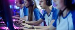 Na fotografia há dois garotos e duas garotas, todos brancos. Eles estão vestindo uma camiseta branca e azul como uniforme. Eles estão em frente a computadores, por onde estão jogando jogos eletrônicos.